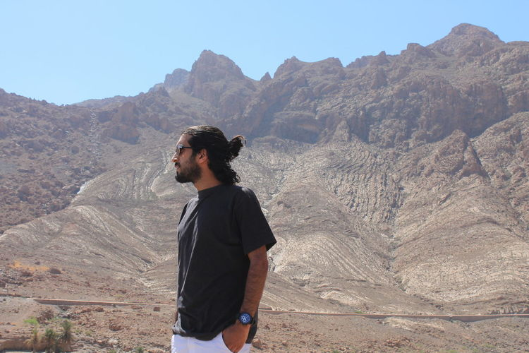 Young man standing against mountain range