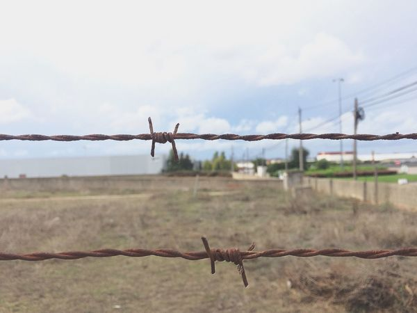 Barbed Wire Barricade Boundary Chainlink Fence Danger Day Fence Focus On Foreground Landscape Metal No People Protection Razor Wire Safety Security Sky Wire