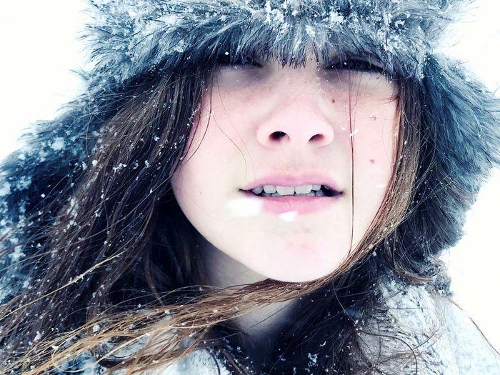 Close-Up Portrait Of Teenage Girl Wearing Fur Hat During Snowfall