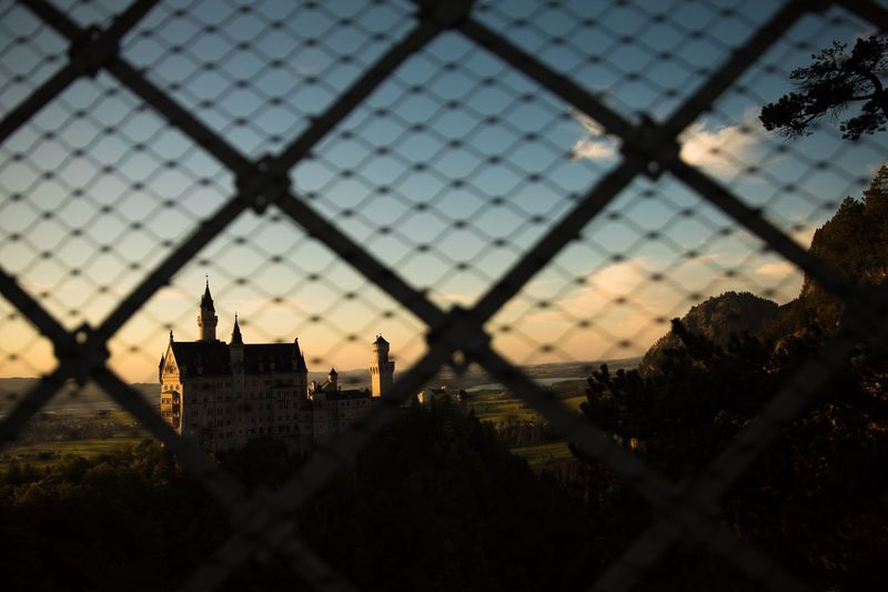 Buildings seen through chainlink fence against sky during sunset