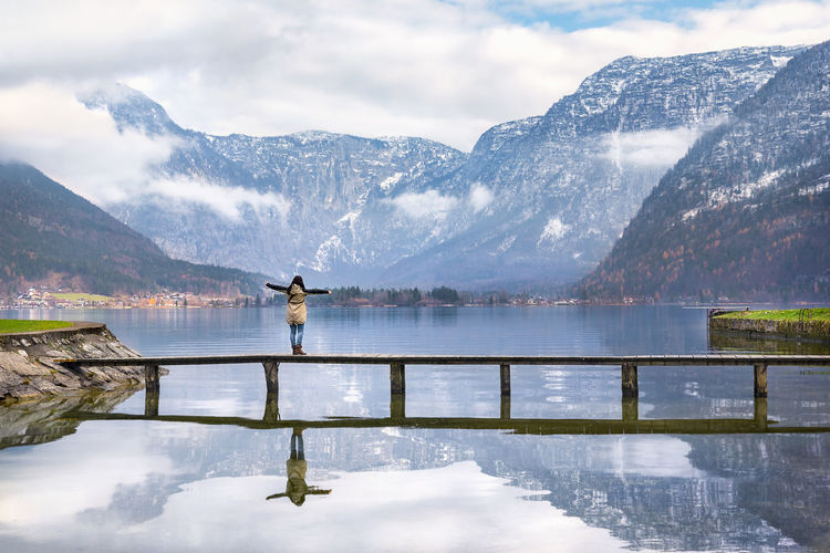 Rear View Of Woman Standing With Arms Outstretched On Bridge Over Lake Hallstatter In Hallstatt Against Mountains