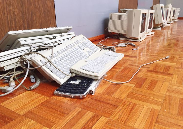 Computer Monitors And Keyboards On Hardwood Floor