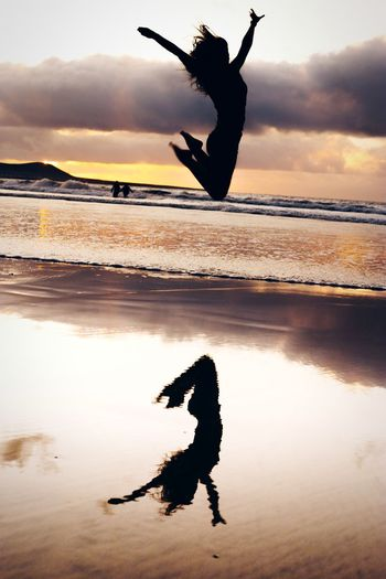 Silhouette man jumping at beach against sky during sunset