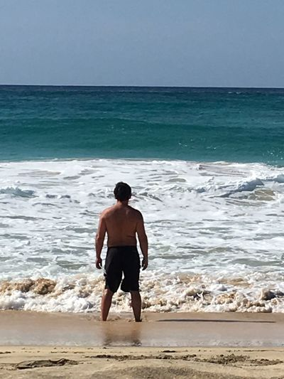 Rear view of shirtless man on beach