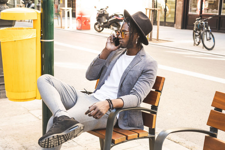 Young man sitting on chair by street in city
