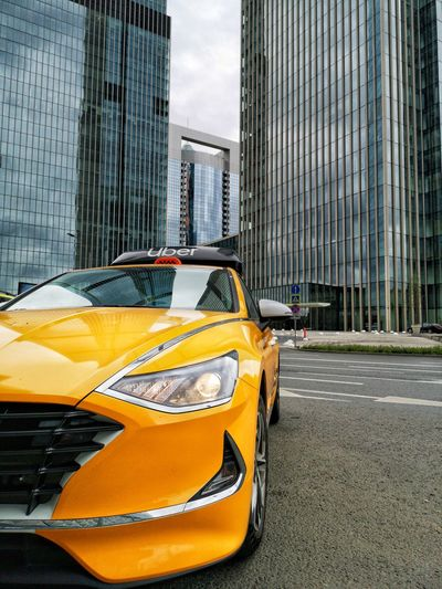 Yellow car on street against buildings