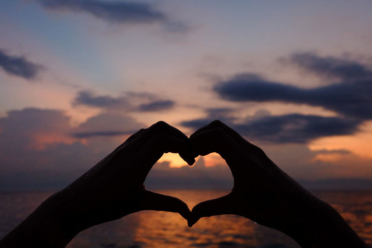 Cropped hands of woman forming heart shape against sea during sunset