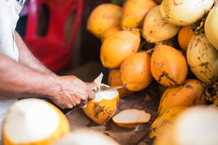 Cropped Hands On Vendor Peeling Coconuts At Market Stall