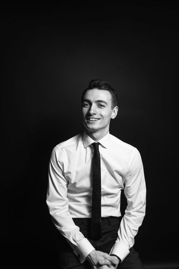 Black And White Black Background Business Business Person Businessman Cut Out Formalwear Front View Happiness Indoors  Looking At Camera Males  Men Menswear One Person Portrait Smiling Studio Shot Three Quarter Length Well-dressed Young Adult Young Men