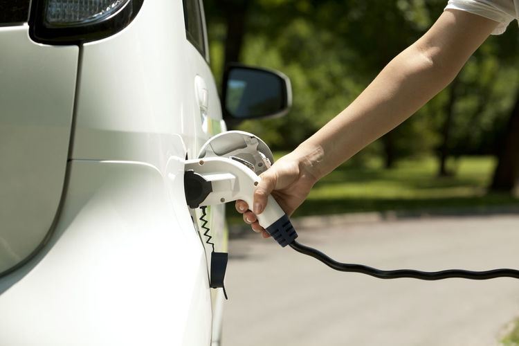 Cropped hand of person charging white electric car