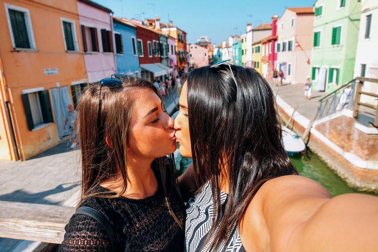 Lesbians kissing by canal in city