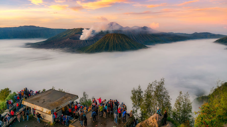 High Angle View Of People On Mountains Against Sky During Sunset
