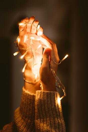 Close-up of woman hand holding illuminated lighting equipment