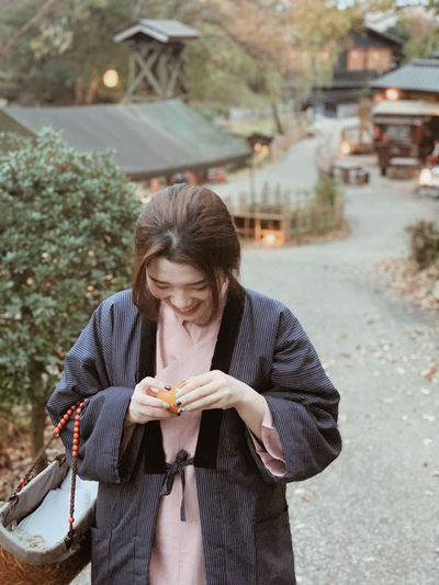 Girl wears japanese traditional clothing  with basket  on arm  is pealing an orange while walking