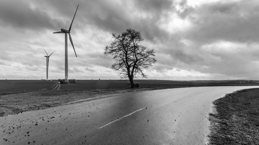 Windmill on road by land against sky