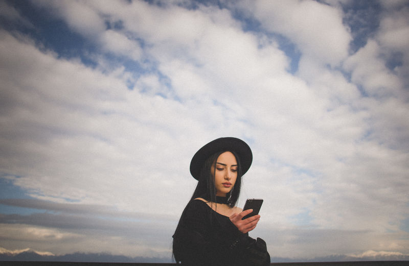 Beautiful young woman using mobile phone standing against sky