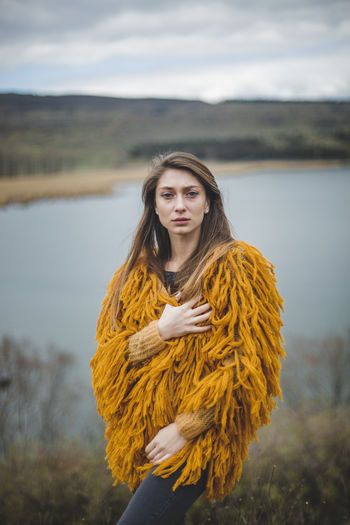 Beautiful Woman Beauty Beauty In Nature Brown Hair Focus On Foreground Hair Hairstyle Leisure Activity Lifestyles Long Hair Looking At Camera Nature One Person Outdoors Portrait Real People Standing Warm Clothing Water Young Adult Young Women