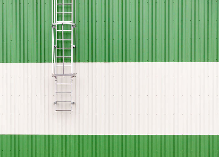 Abstract minimalist architecture picture with metal warehouse wall and metal ladders Copy Space Industry Industrial Geometric Geometry Wall - Building Feature Ladder Architecture Minimalism Abstract Corrugated Iron Textured  Backgrounds Close-up Green Color Corrugated Abstract Backgrounds Building Exterior Step Ladder