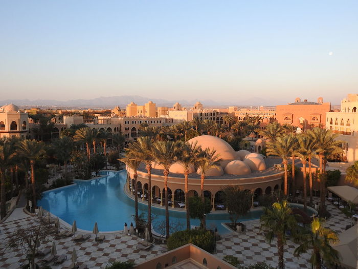 High angle view of palm trees and dome building by swimming pool