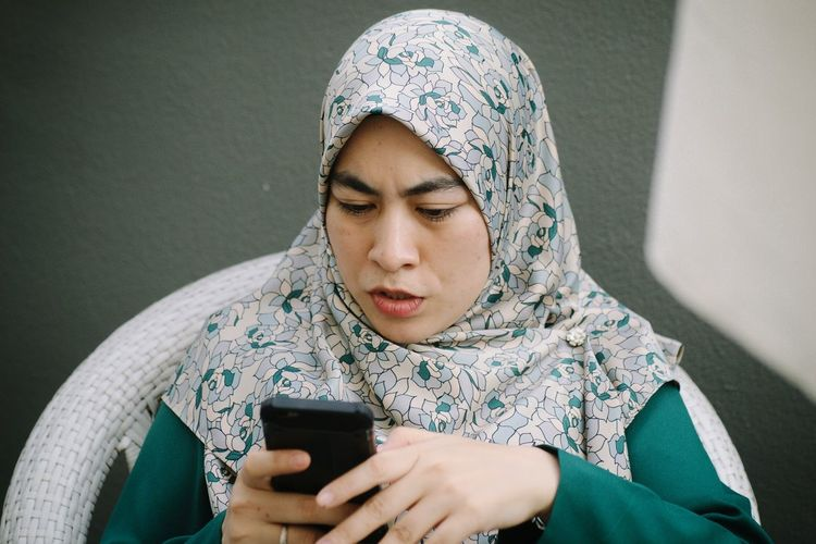 Woman in hijab using mobile phone against wall