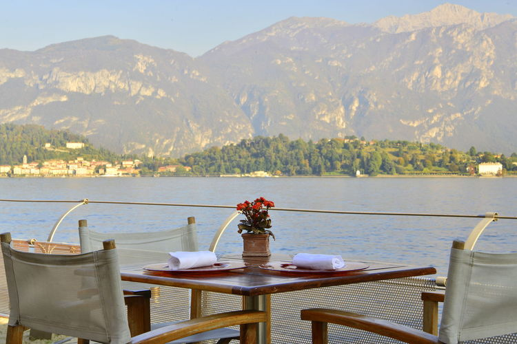 Chairs and table by lake against mountains