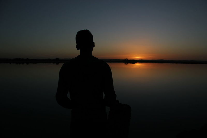 Egypt Travel Destinations Silhouette Sunset Reflection One Person Dark Rear View People Standing Sky Water Tranquility One Man Only Adult Beauty In Nature Horizon Over Water Night Sea Nature Siwa Oasis Egypt Clear Sky Scenics Lake Outdoors