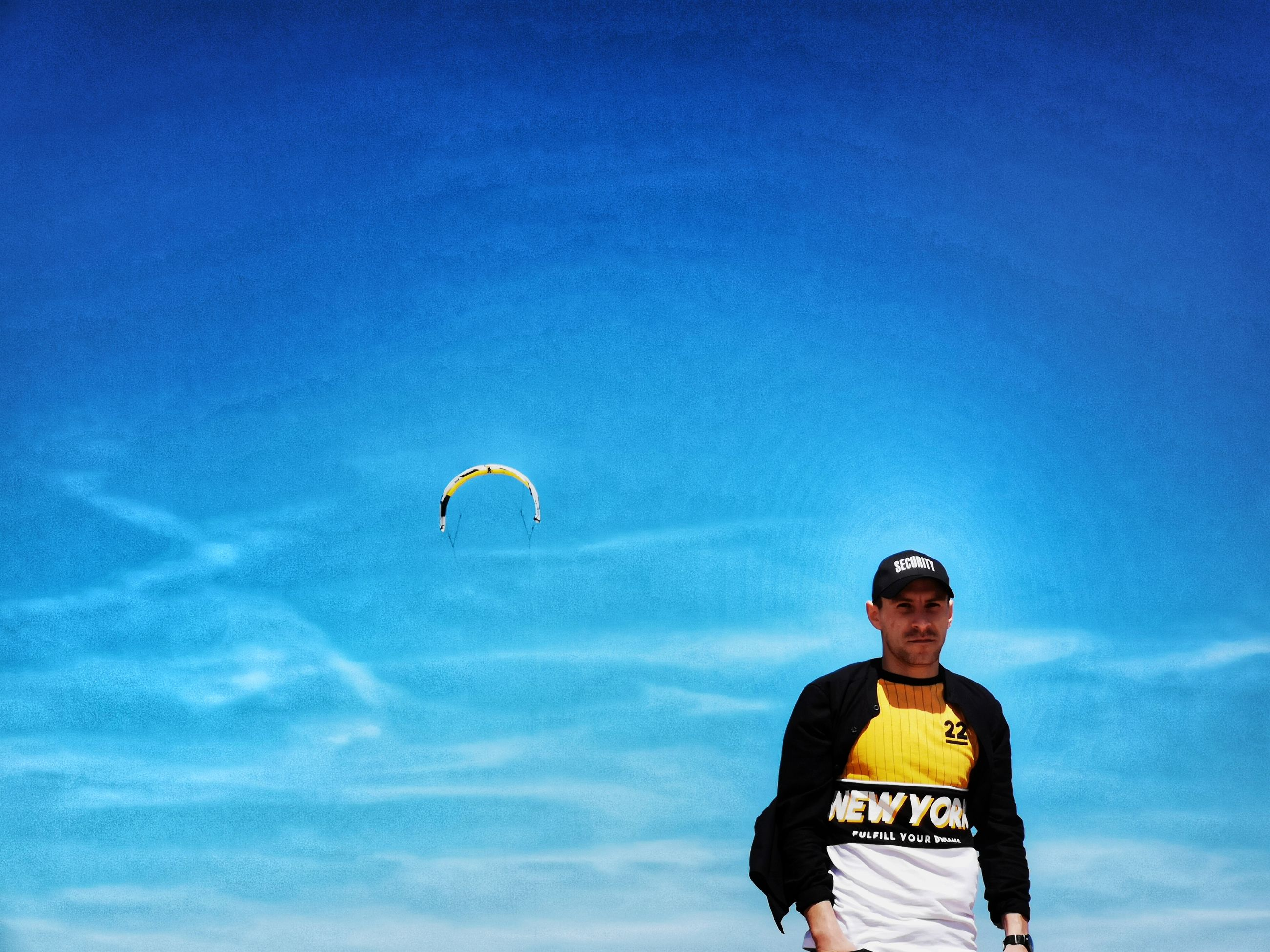 sky, one person, leisure activity, low angle view, sport, blue, front view, cloud - sky, parachute, real people, day, standing, flying, lifestyles, nature, three quarter length, paragliding, extreme sports, glasses