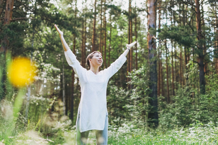 Woman with arms raised standing amidst trees