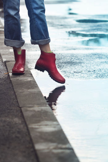 Low Section Of Woman On Footpath By Puddle