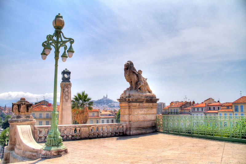 View of lion statue and lamp post against roofed structures