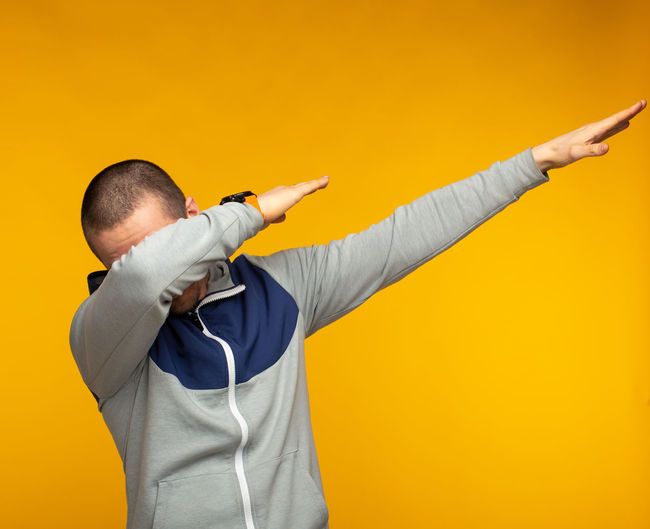 Man in hoodie show swag standing at orange background. Funny sign. Colored Background Studio Shot One Person Yellow Standing Men Indoors  Holding Waist Up Yellow Background Copy Space Human Arm Limb Adult Casual Clothing Human Body Part Arms Raised Males  Orange Color Orange Background Skill  Human Limb Beige Background Swag