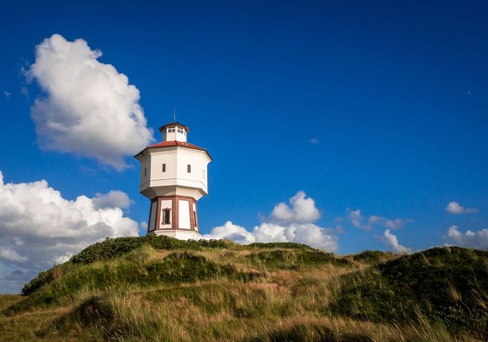 Building Exterior Sky Lighthouse Nature Built Structure Blue Architecture Cloud - Sky Beauty In Nature Low Angle View Tree Day Landscape No People Outdoors Growth Scenics Grass Langeoog