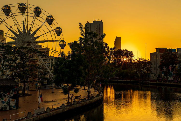 Ferris wheel by river against buildings in city at sunset