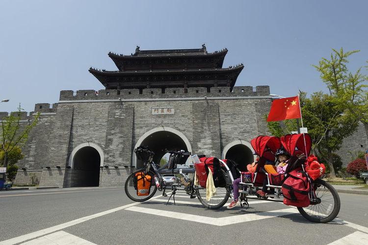 Siblings sitting in baby stroller against temple