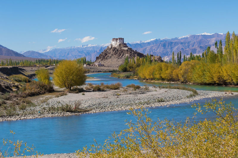 Scenic view of river and landscape against blue sky