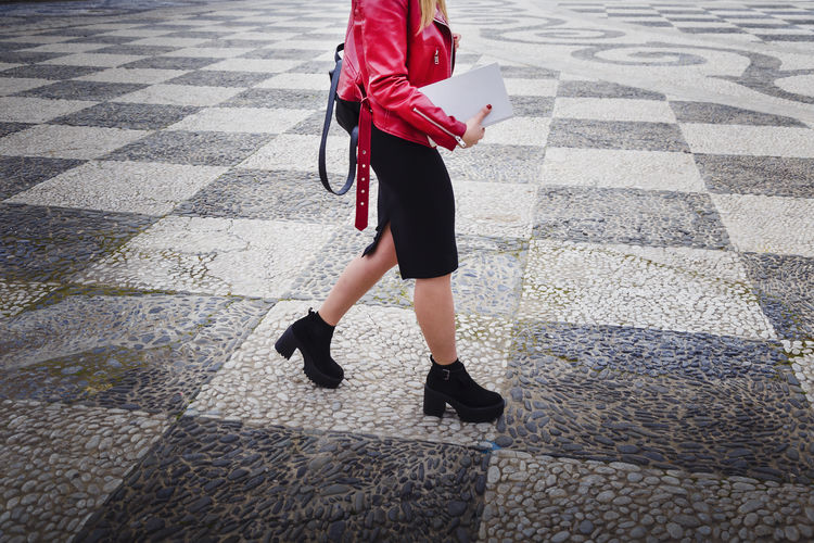 Young woman dressed in black and a red jacket walking down the street with a white book in her hand