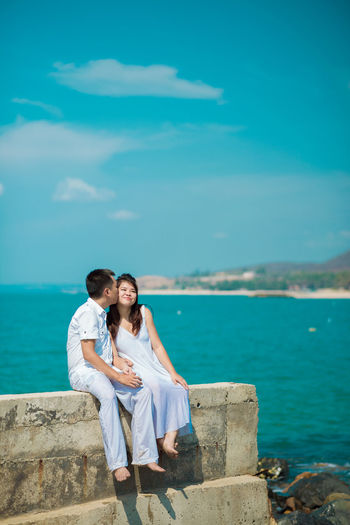 Man Kissing Woman While Sitting Against Sea