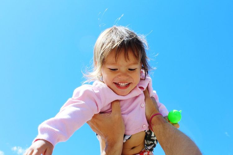 Cropped hands of man lifting daughter against clear blue sky
