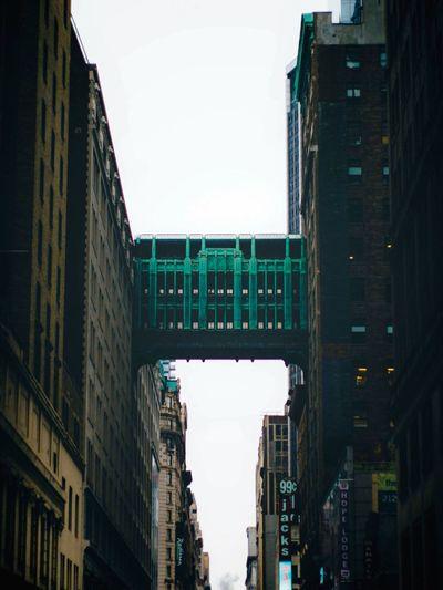 Low Angle View Footbridge Amidst Buildings