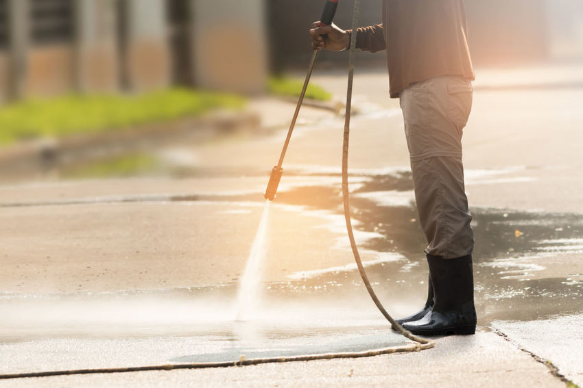 High pressure deep cleaning. Worker cleaning driveway with gasoline high pressure washer ,professional cleaning services. Washing Worker Cleaning Services Driveway High Pressure Cleaner Jet Outdoors Professional Occupation Water Wet