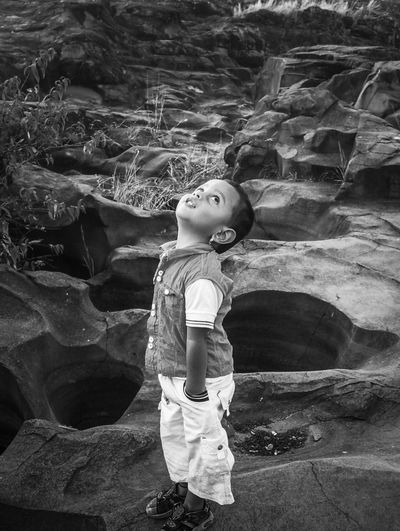 Cute boy looking up while standing on rocks