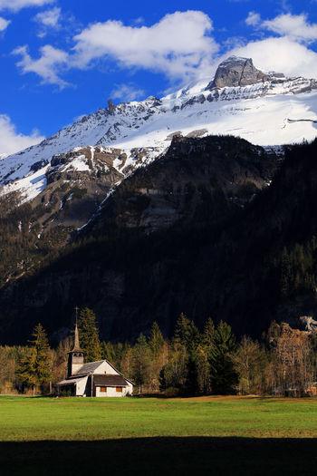 Church on field against snowy mountains