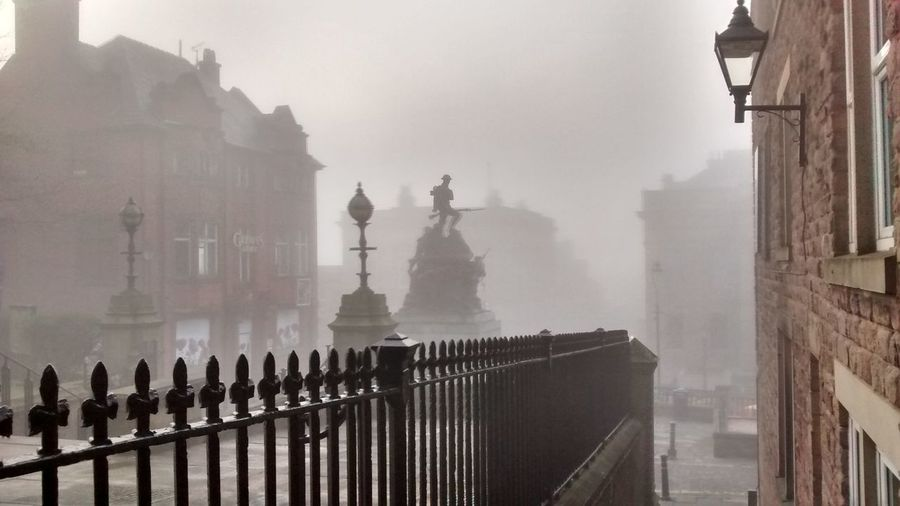 Buildings in city during foggy weather