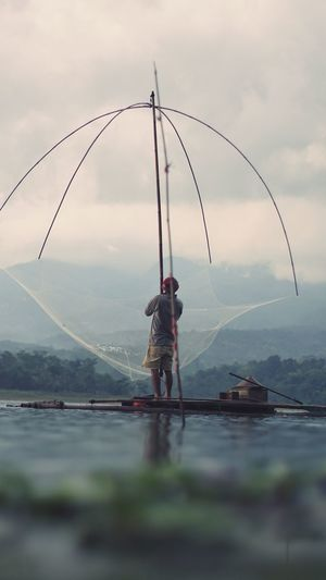 Rear view of man fishing against sky