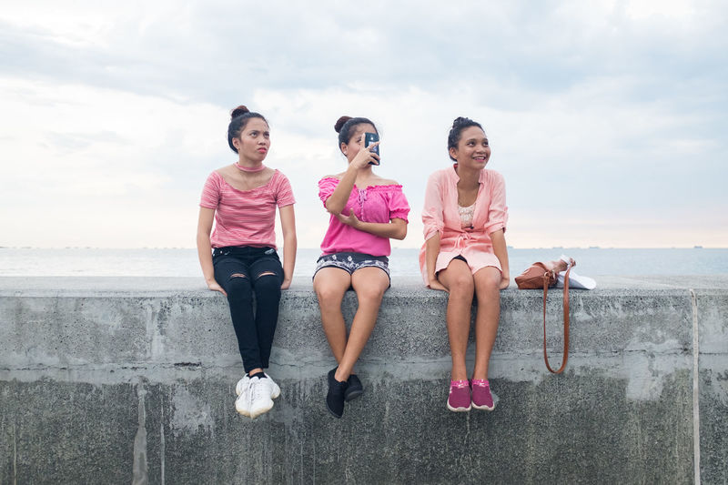 Beach Casual Clothing Cloud - Sky Day Friendship Front View Full Length Happiness Leisure Activity Lifestyles Nature Outdoors People Pink Color Portrait Real People Sea Sitting Sky Smiling The Portraitist - 2017 EyeEm Awards Togetherness Young Adult Young Women