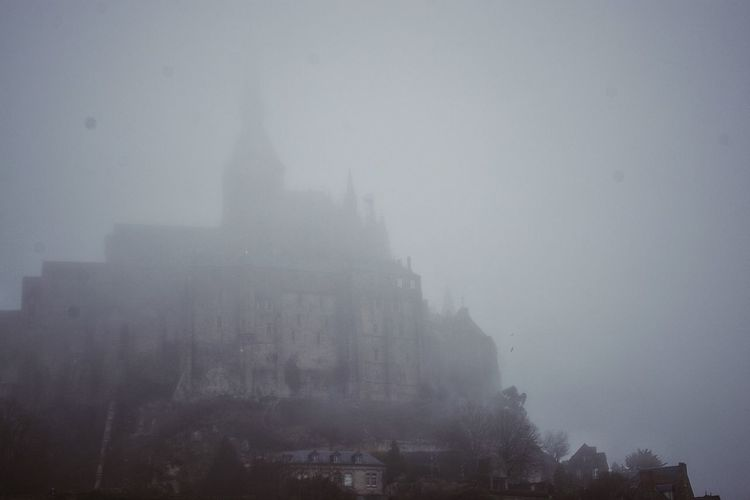 Just like taken out of a horror movie, Mont Saint-Michel greets me. Fog Horror Landscapes Cathedral Abbaye Abbey Hunted Scenery Scary Medival History Architecture Tenebrous Murky Scene Dark Gloomy Weather Spooky Rainy Days The Architect - 2016 EyeEm Awards Bretagne Weather Mist Haze Showcase: February Misty Landscape Historical Building Historical Site