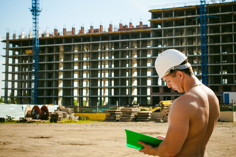 Shirtless Man Standing Against Construction Buildings