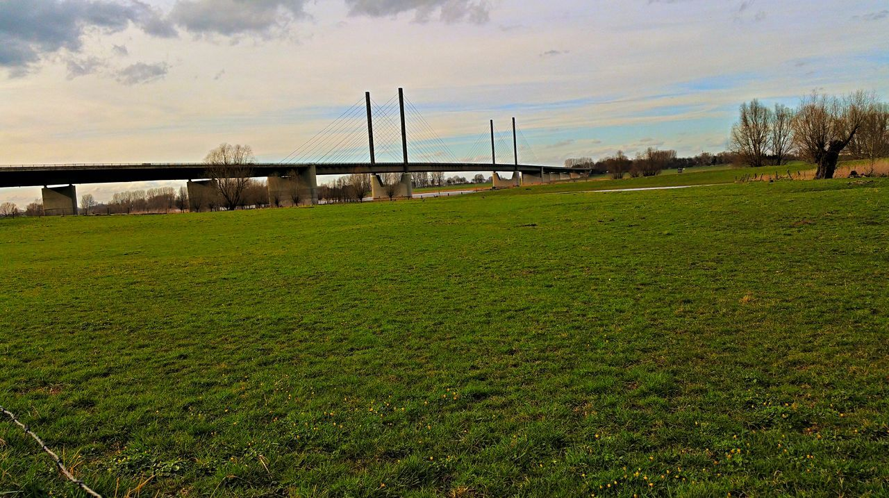 bridge - man made structure, grass, connection, sky, built structure, architecture, field, growth, cloud - sky, river, nature, day, water, outdoors, green color, transportation, no people, scenics, tree, beauty in nature