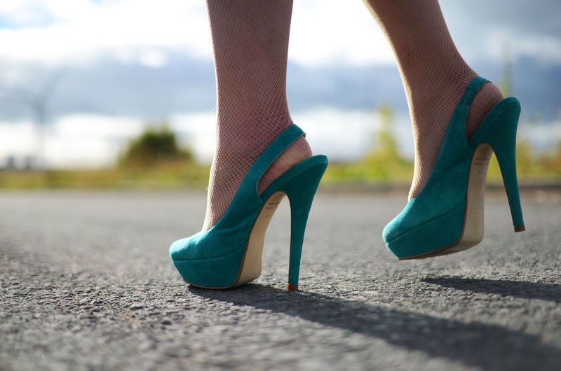Low Section Of Woman Wearing High Heels Standing On Road