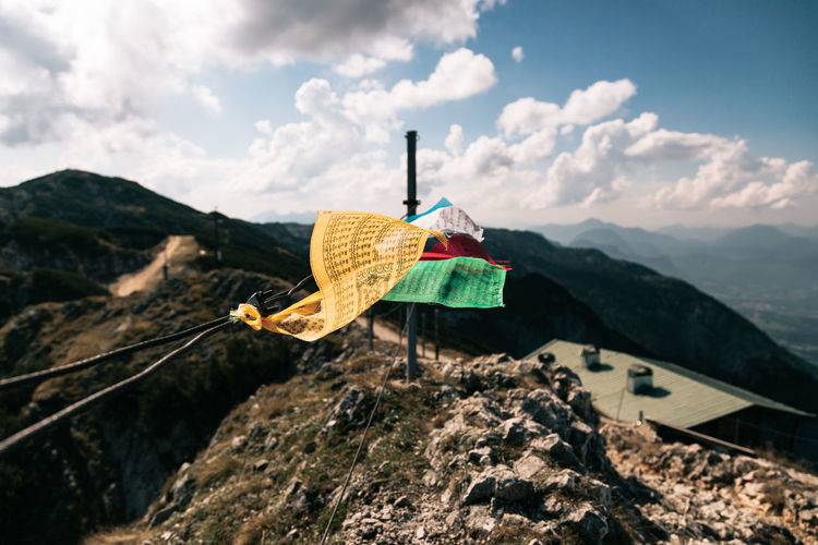 Close-up of umbrella hanging on mountain against sky
